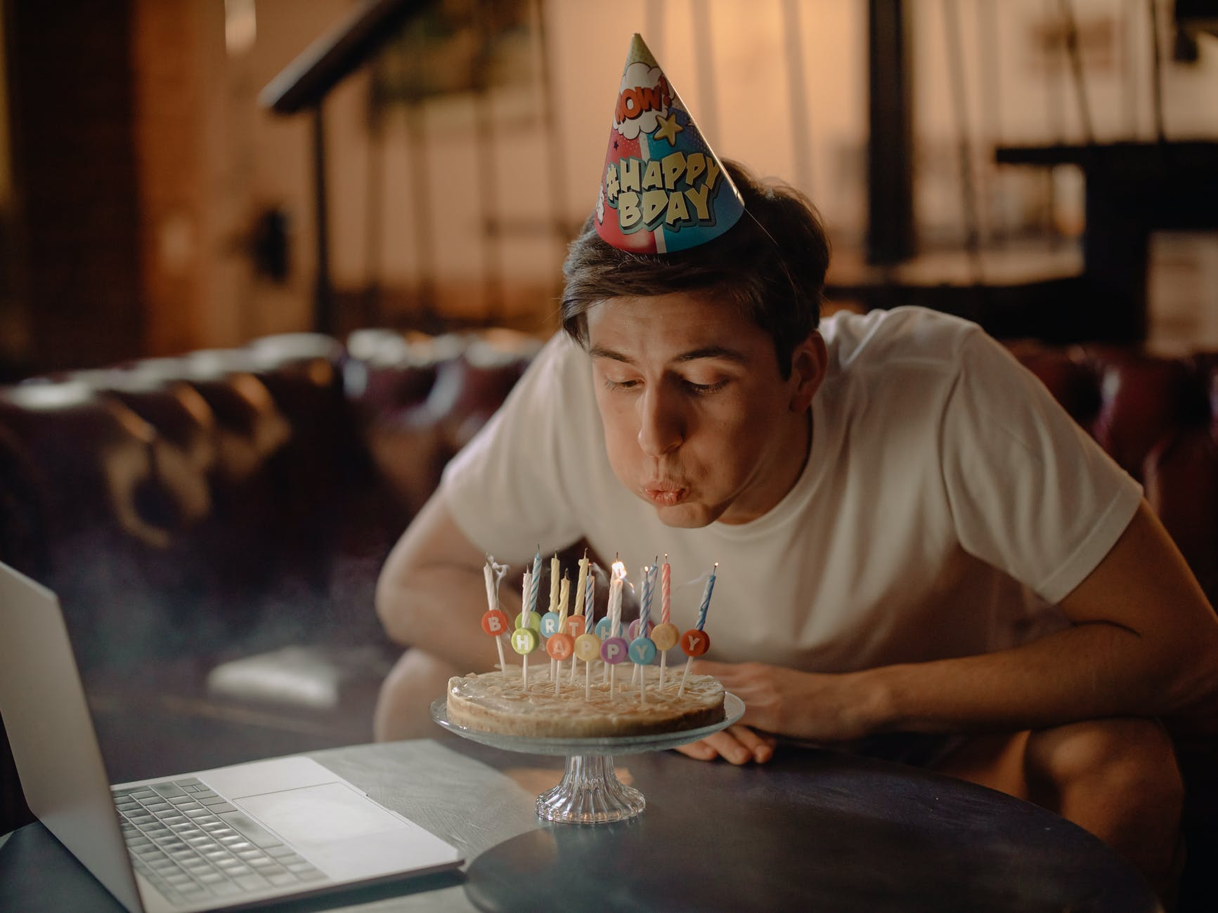 man in white crew neck t shirt sitting by the table with cake